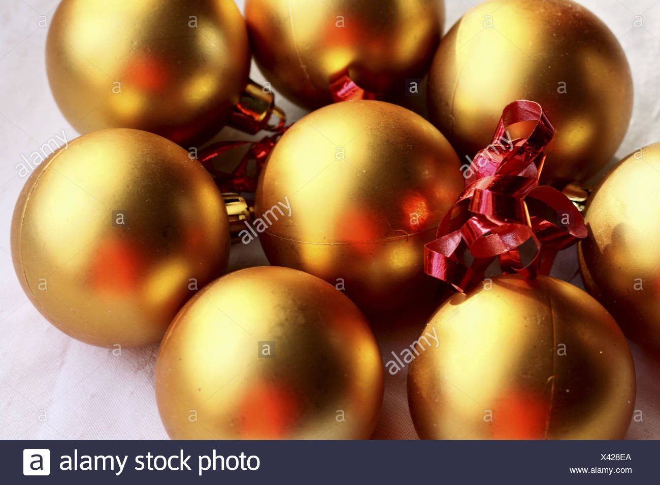 gold christmas balls with red ribbon on white linen gold balls reflect the highlights of red ribbon - Red And Gold Christmas Ornaments