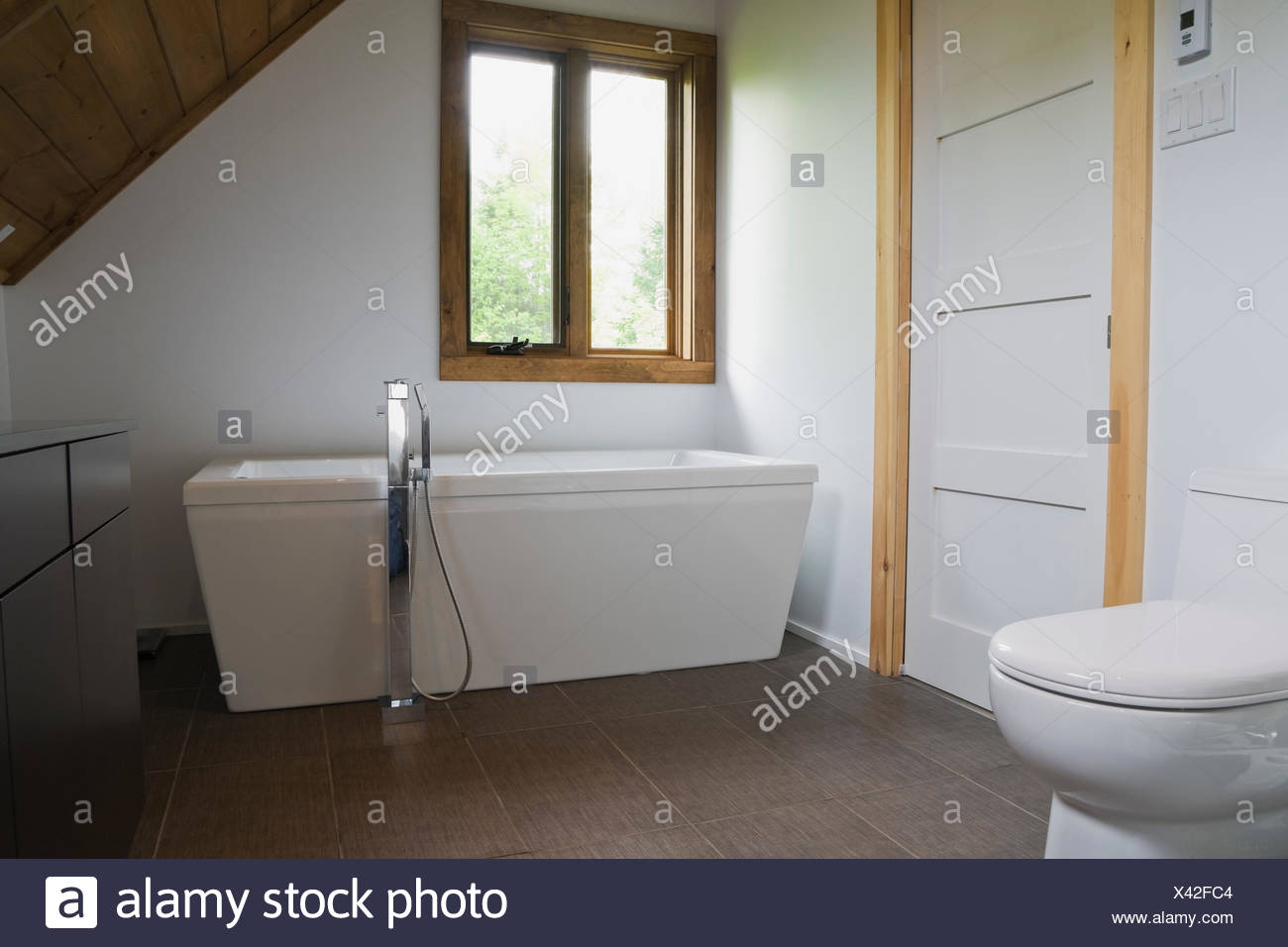 Bathroom with grey ceramic tile floor, white porcelain toilet and ...
