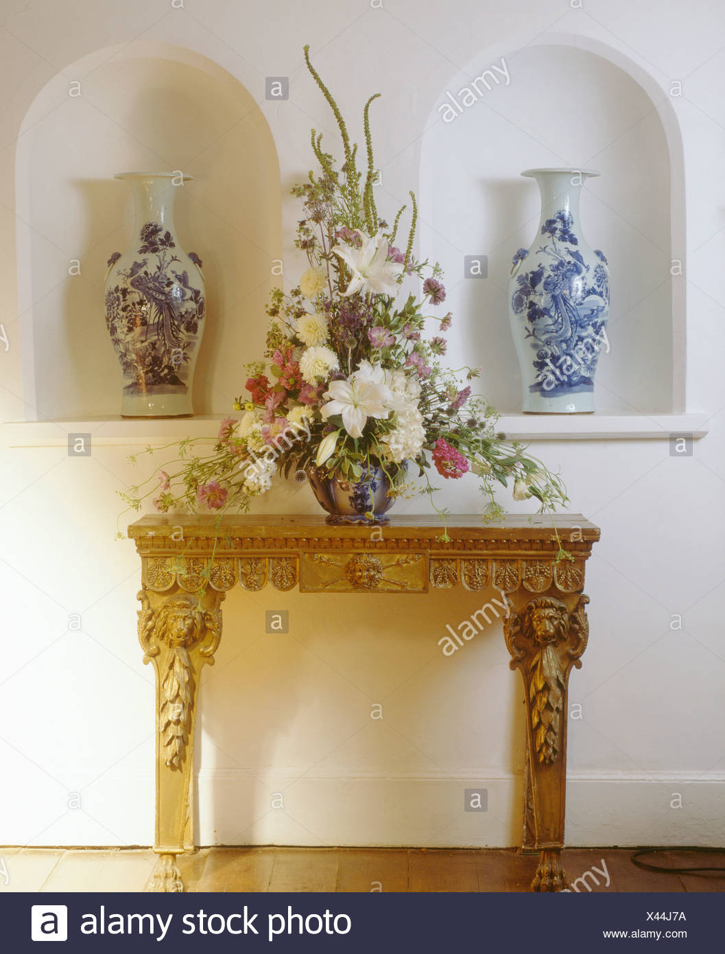 White lilies in fresh floral arrangement on console table in front white lilies in fresh floral arrangement on console table in front of alcoves with tall blue and white vases izmirmasajfo