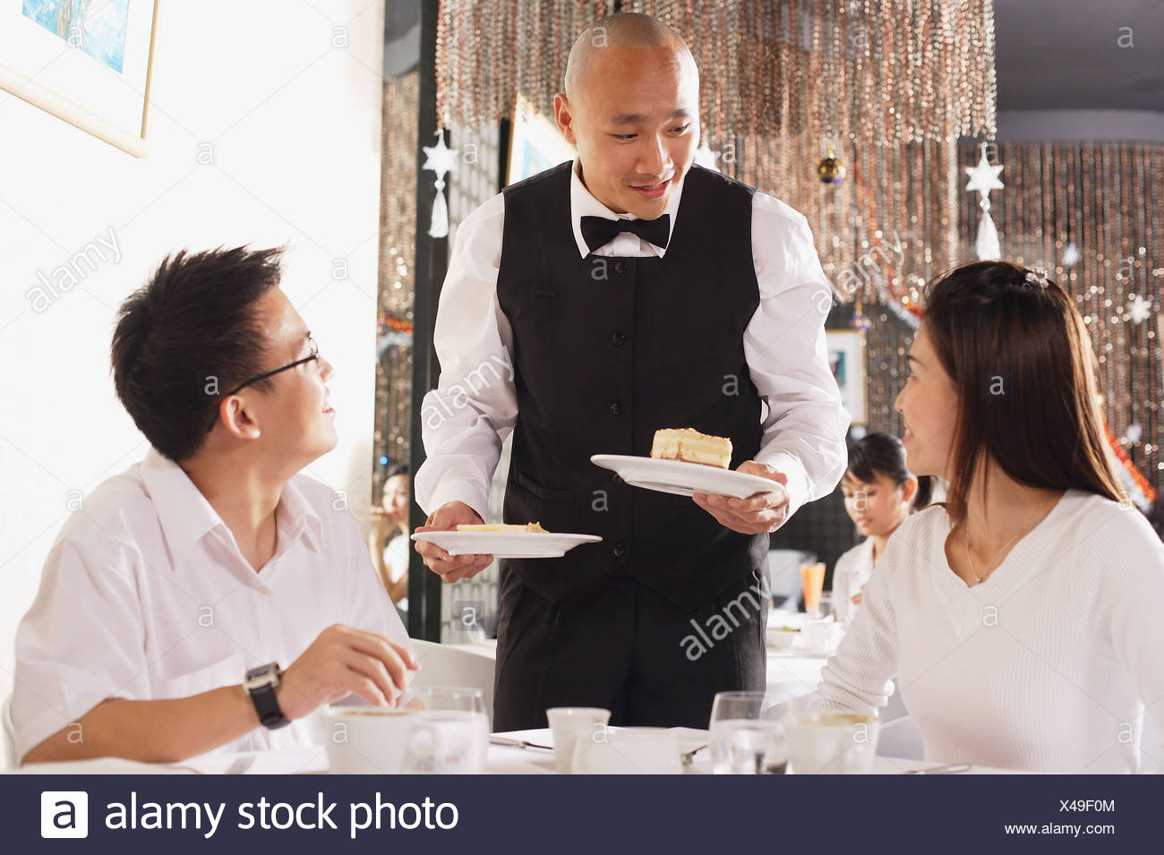 couple in restaurant waiter standing holding plates of dessert