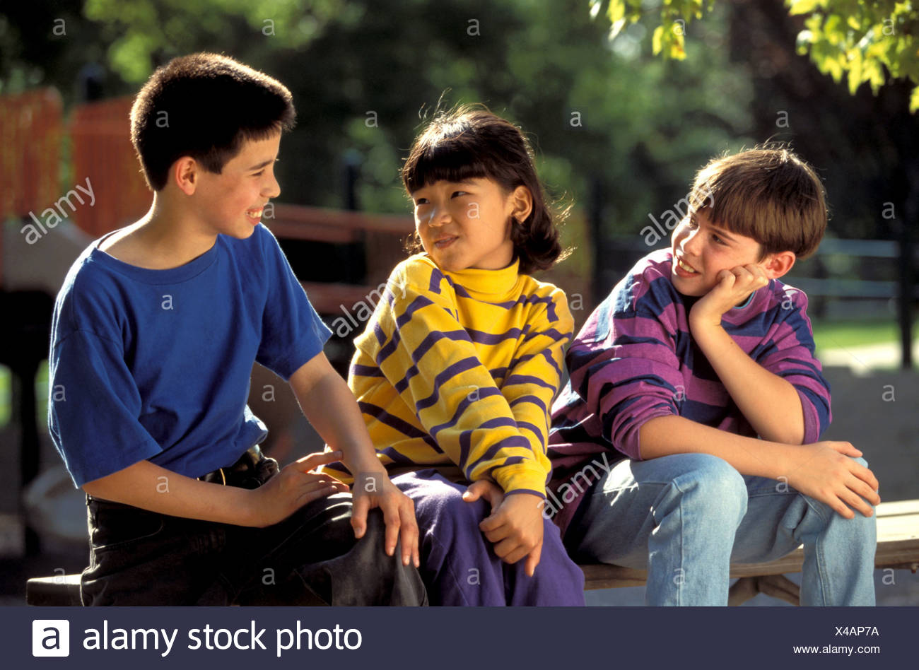 three children of different nationalities sitting on a bench