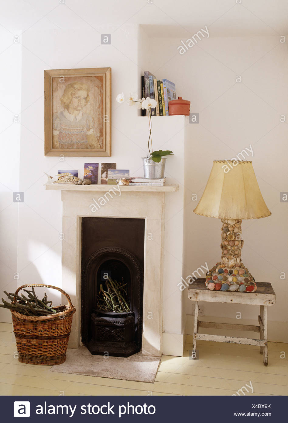 Pebble Encrusted Lamp On Painted Stool Beside Small Fireplace In White  Bedroom With Basket Of Firewood