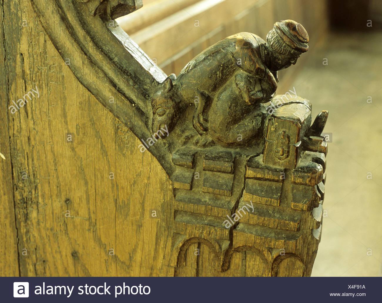Medieval bench end man in stocks with stolen pig hog across shoulder