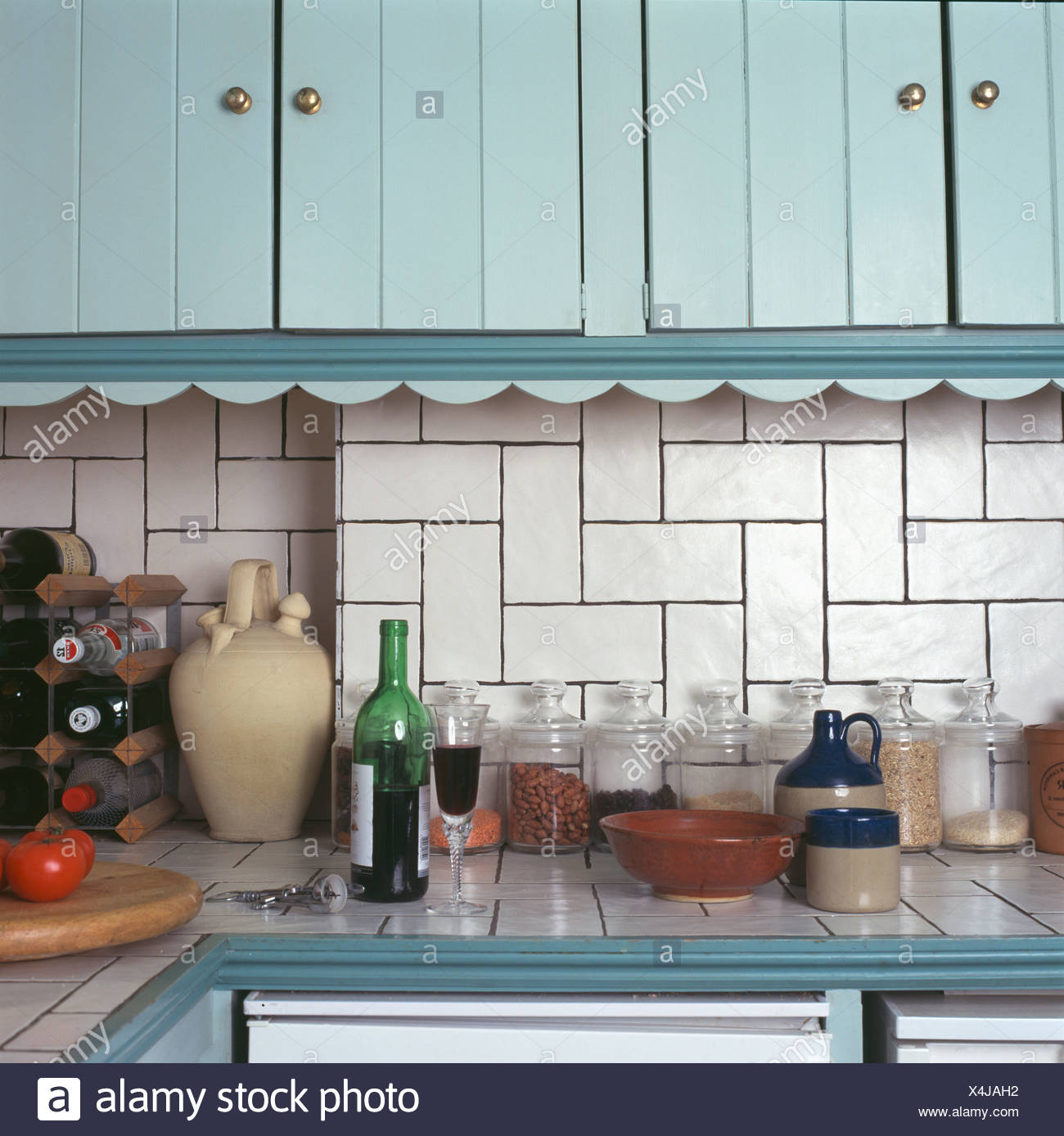 Close-up of glass jars on worktop below turquoise cupboards and ...
