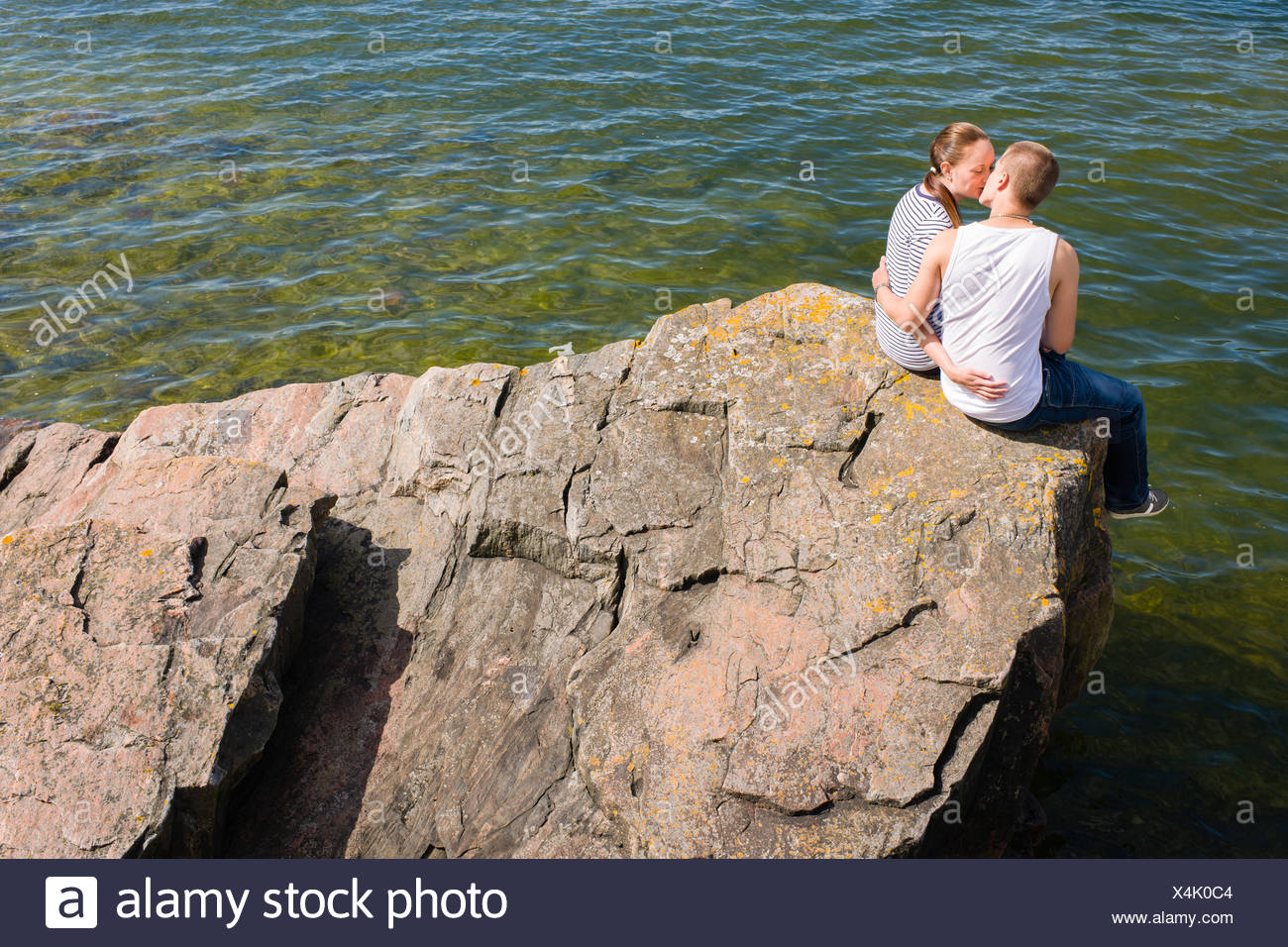 Young Lovers Sitting And Kissing On The Big Rock