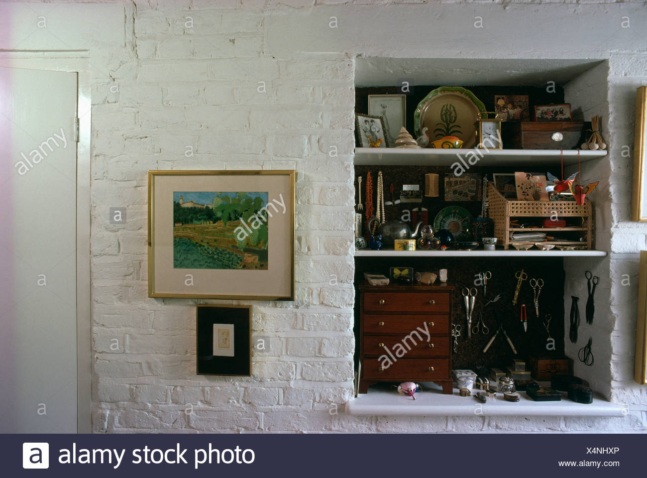 Cluttered alcove shelves in cottage hall with picture on white ...