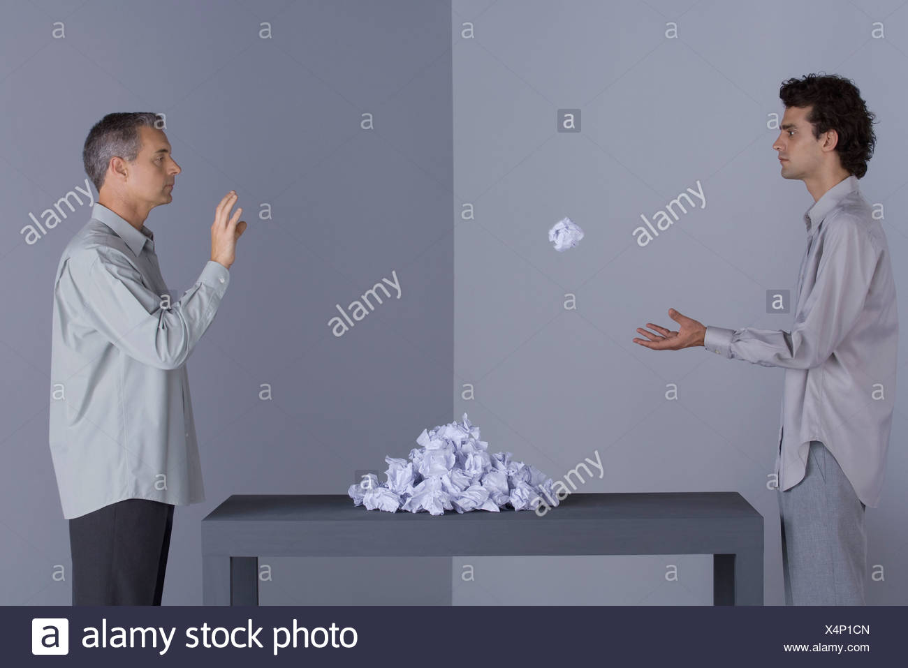 two men standing face to face, one throwing paper ball, pile of