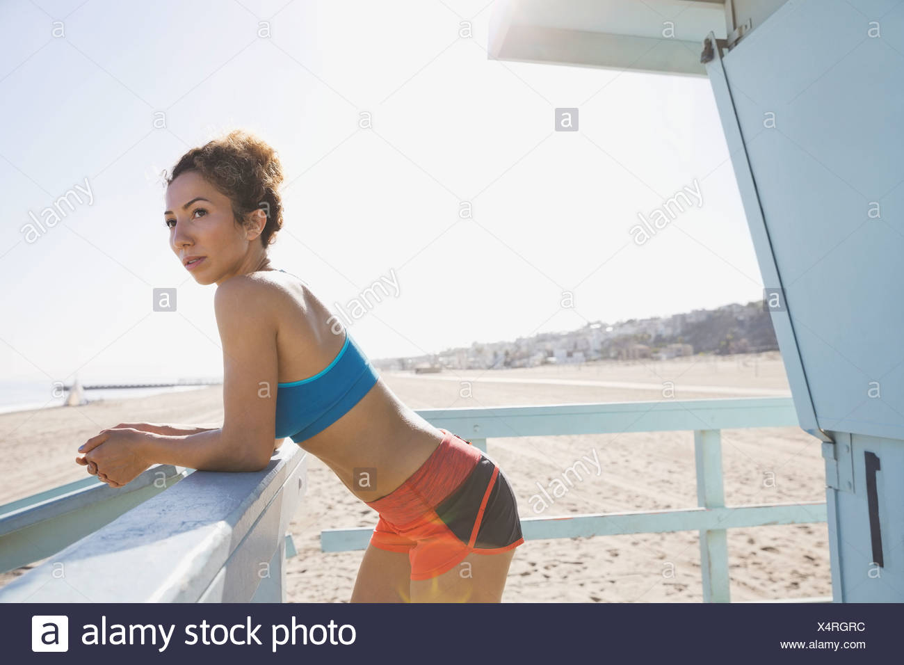 thoughtful woman leaning against railing on beach stock photo