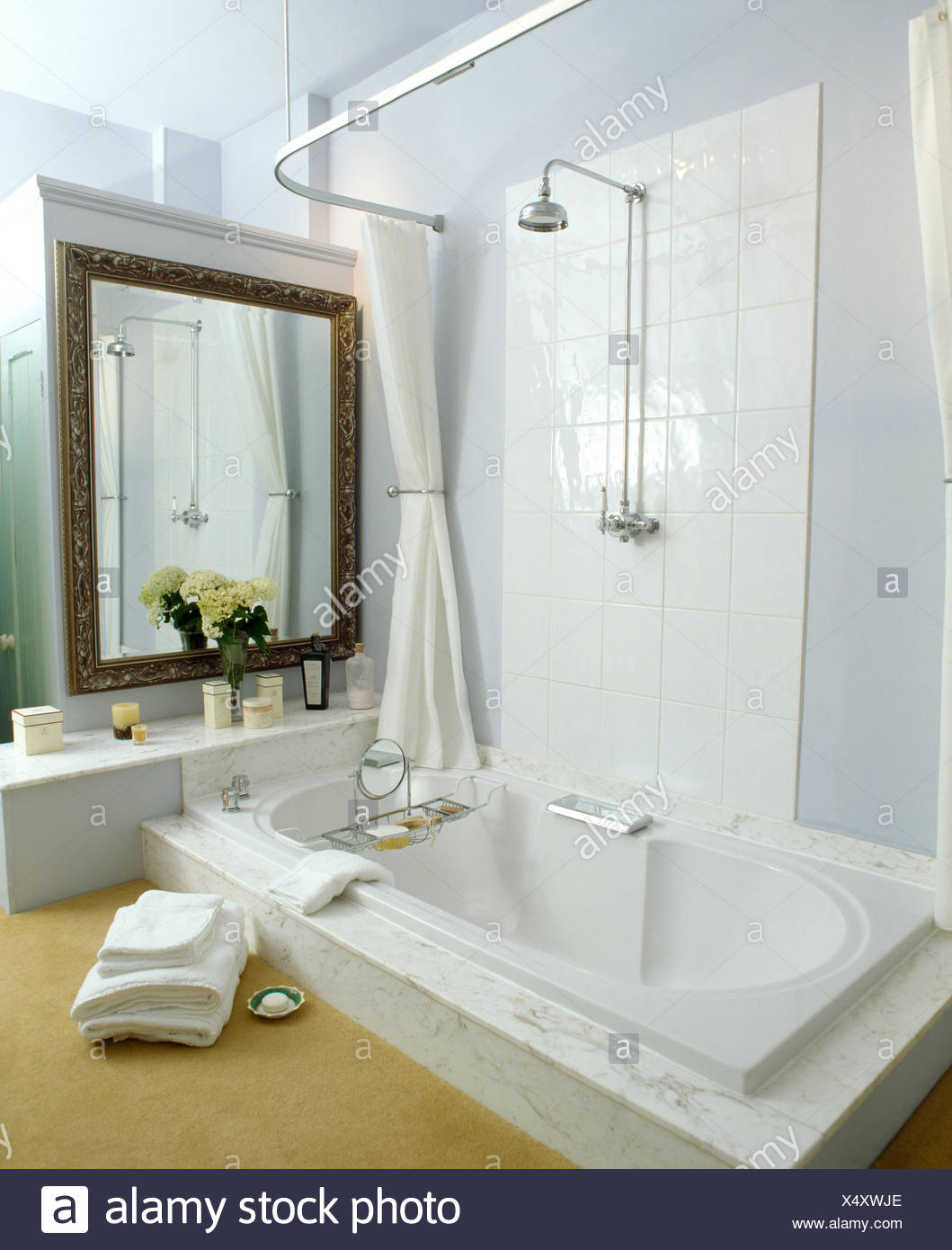 Pile of white towels beside bath with chrome shower in modern white ...