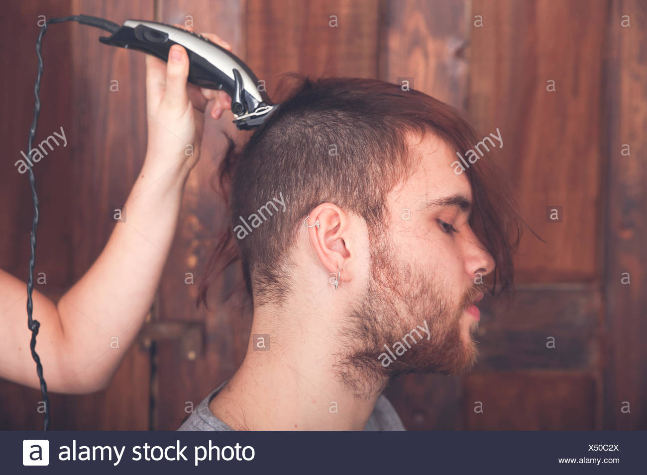 Young Man Getting A Haircut By His Girlfriend With Hair Cutting