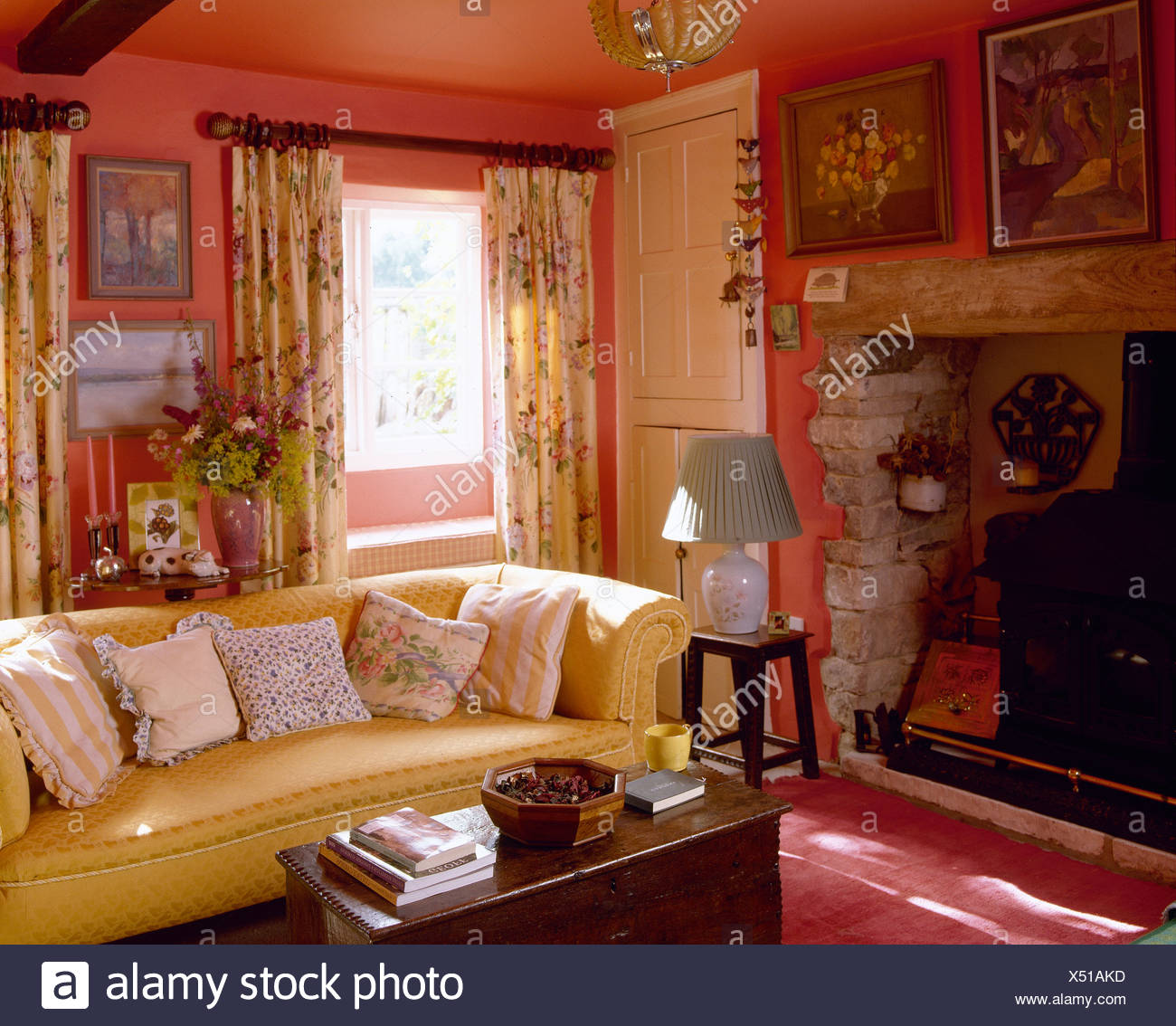 Yellow Sofa With Floral Cushions In Cheerful Red Country Sitting Room With  Inglenook Fireplace And Floral Curtains