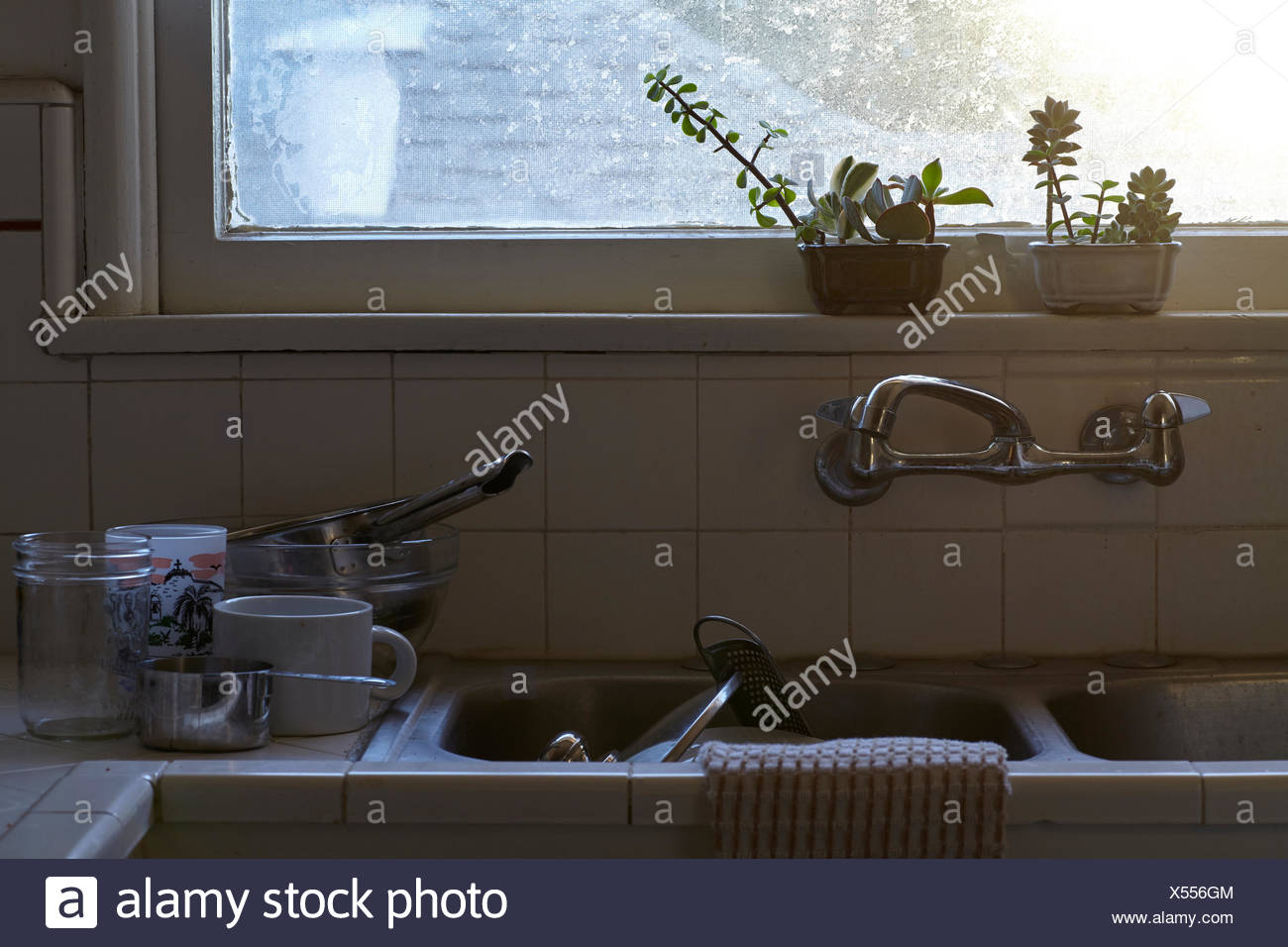 Dirty washing up stacked in kitchen sink and counter Stock Photo ...