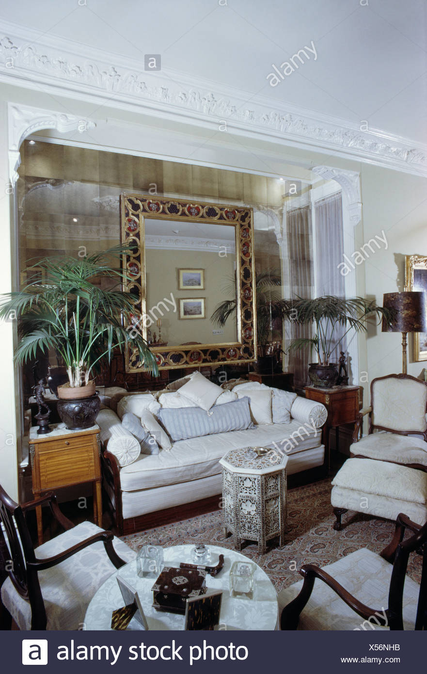 Large mirror in alcove above traditional white sofa in sixties living room