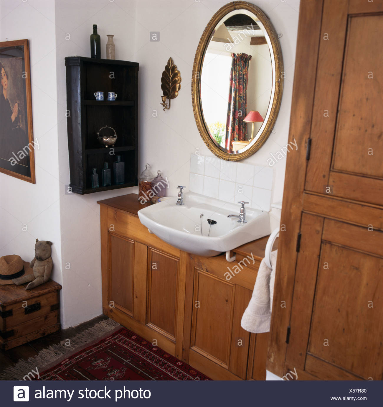 Oval Mirror Above Basin In Fitted Wood Vanity Unit In Small White Bathroom  With Antique Shelves
