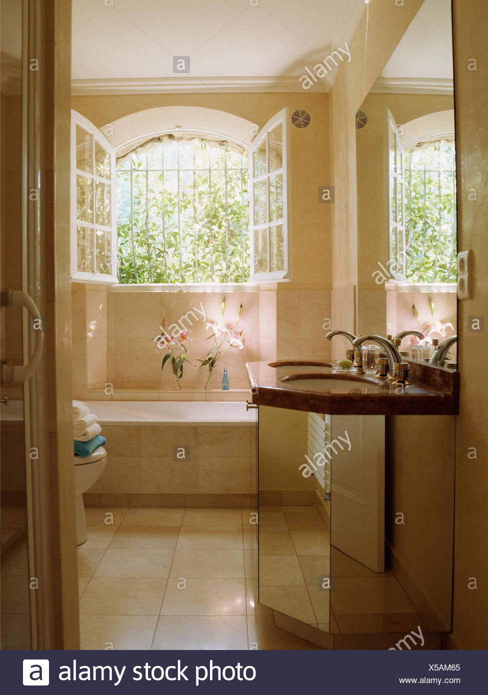 Open Windows Above Bath In French Country Bathroom With Basin In Mirrored  Vanity Unit