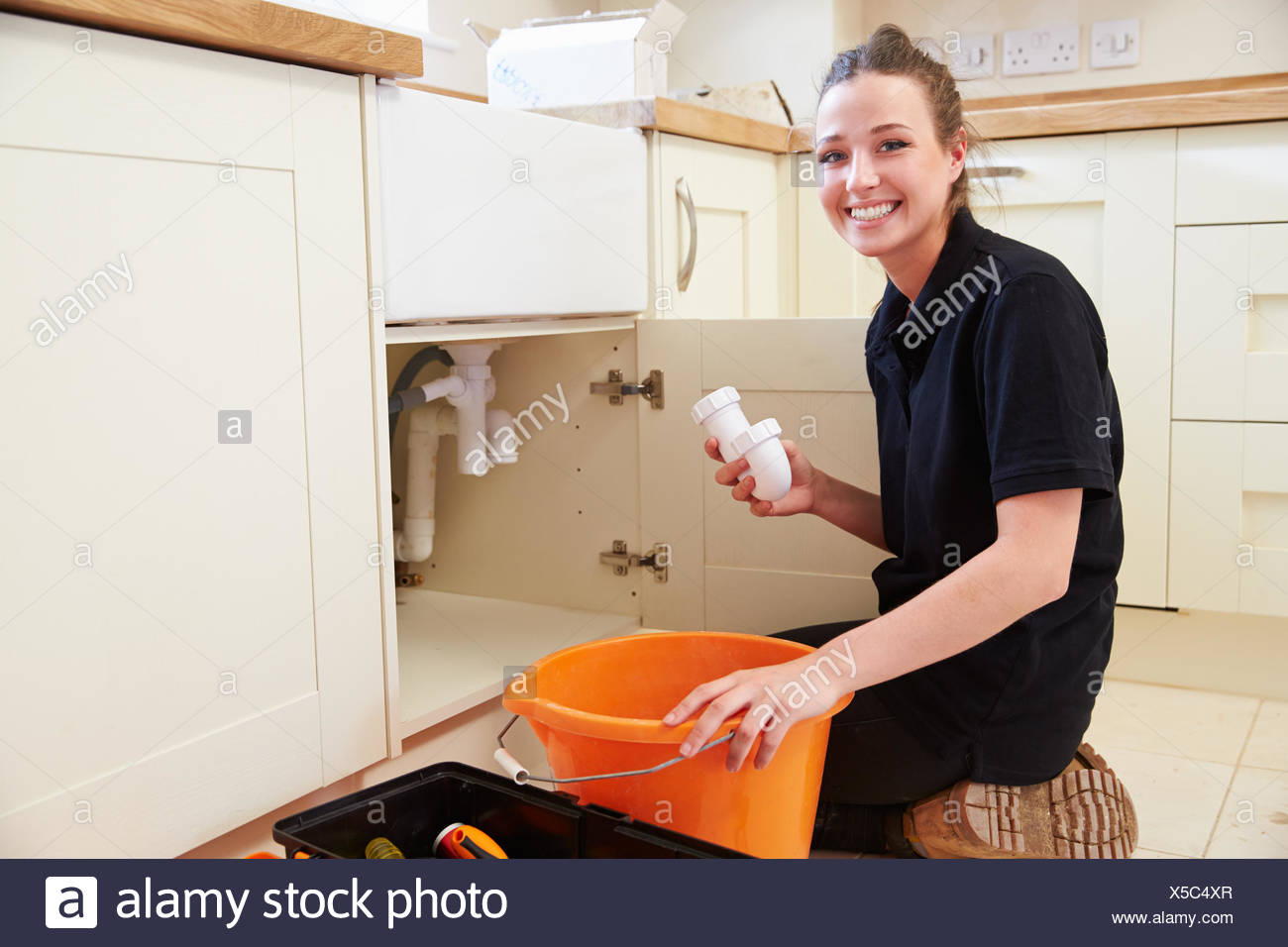 Female plumber holding a u-bend pipe for a kitchen sink Stock Photo ...