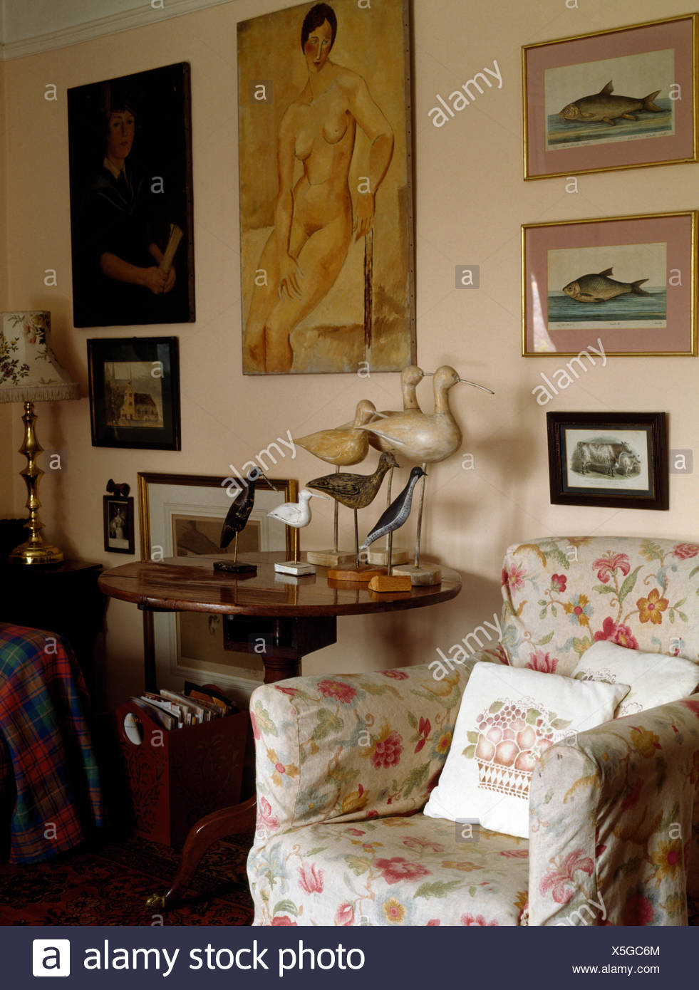 Floral Loose Cover On Armchair Beside Table With Decoy Ducks In Old  Fashioned Living Room