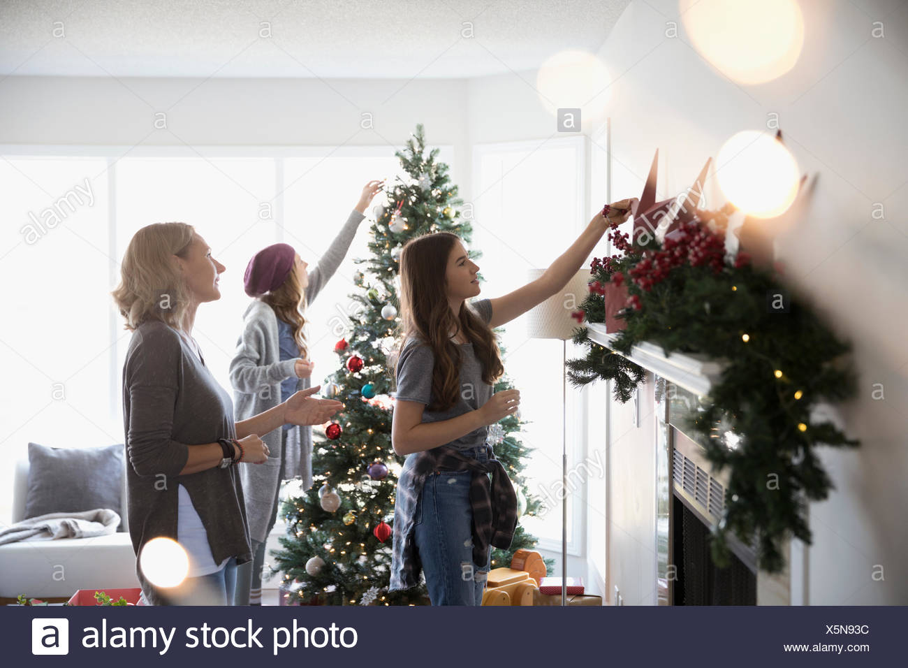 mother and daughters decorating christmas tree and hanging garland on fireplace mantle in living room - Hanging Garland Christmas Decorations