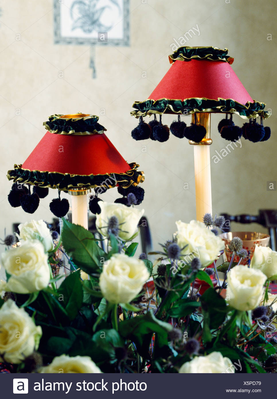 Close Up Of White Roses In Front Of Lamps With Red Silk Shades
