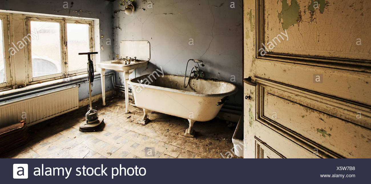 Interior view of abandoned bathroom, ball and claw tub and sink ...