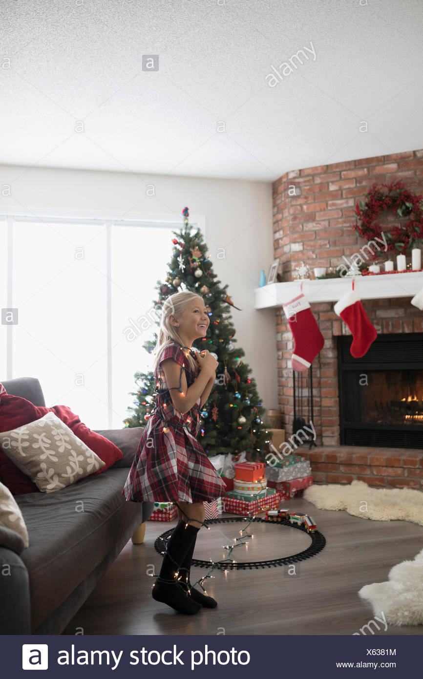 Playful Girl With String Lights Decorating Christmas Tree In Living Room