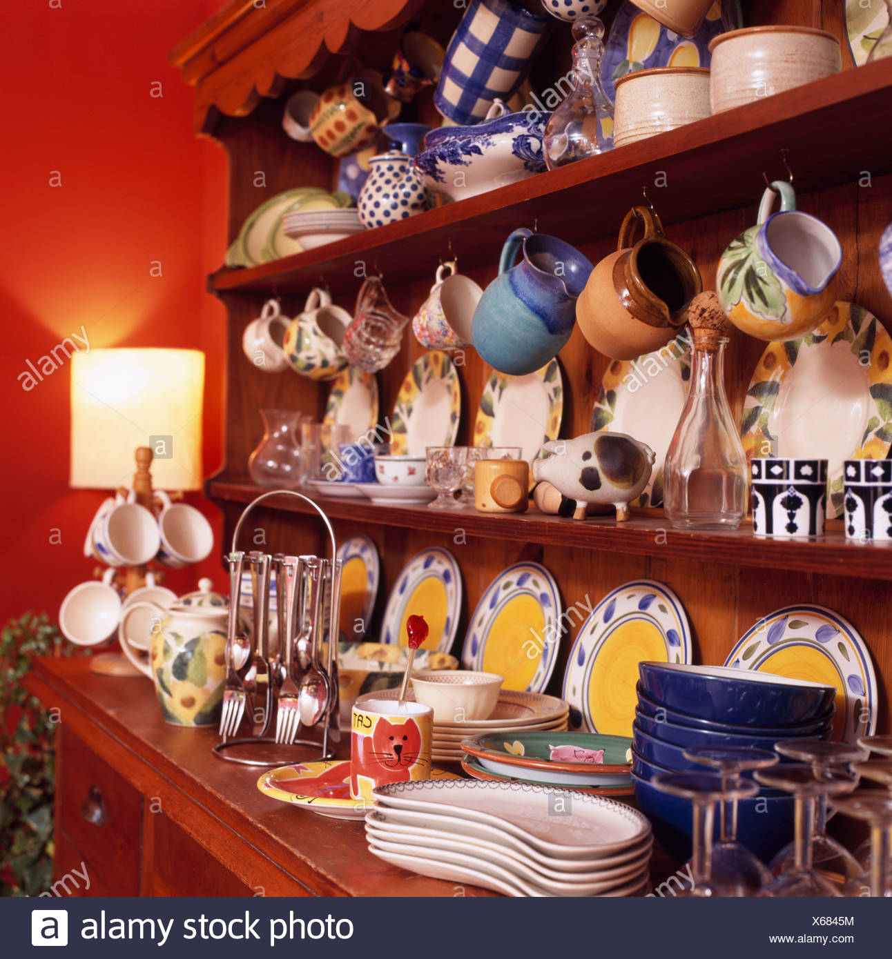 Dresser With Colourful Crockery On Shelves In Red Dining Room