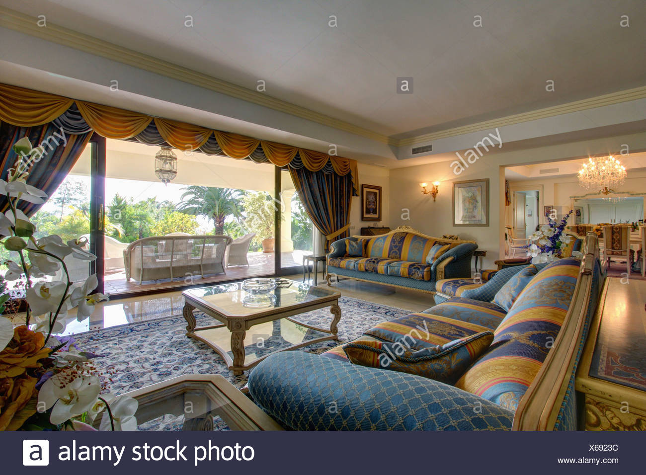 Yellow+blue Patterned Sofa And Matching Drapes On Glass Doors In Spanish  Living Room With Glass Coffee Table