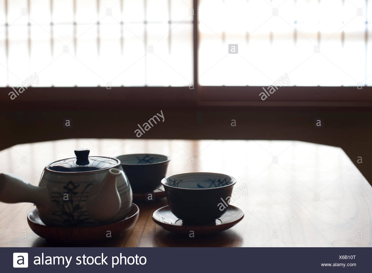 a silhouette image of two japanese tea cups and a tea pot with a