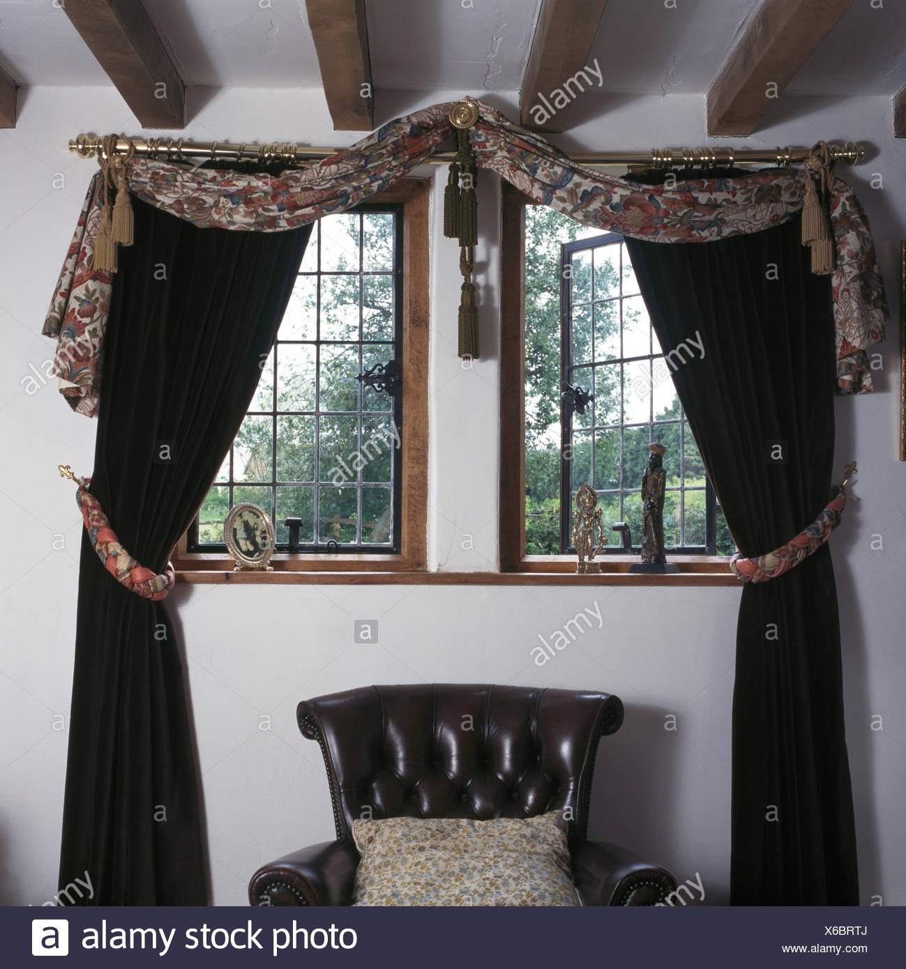 Draped Fabric And Black Curtains On Lattice Window Above Black Leather  Chair In Nineties Bedroom
