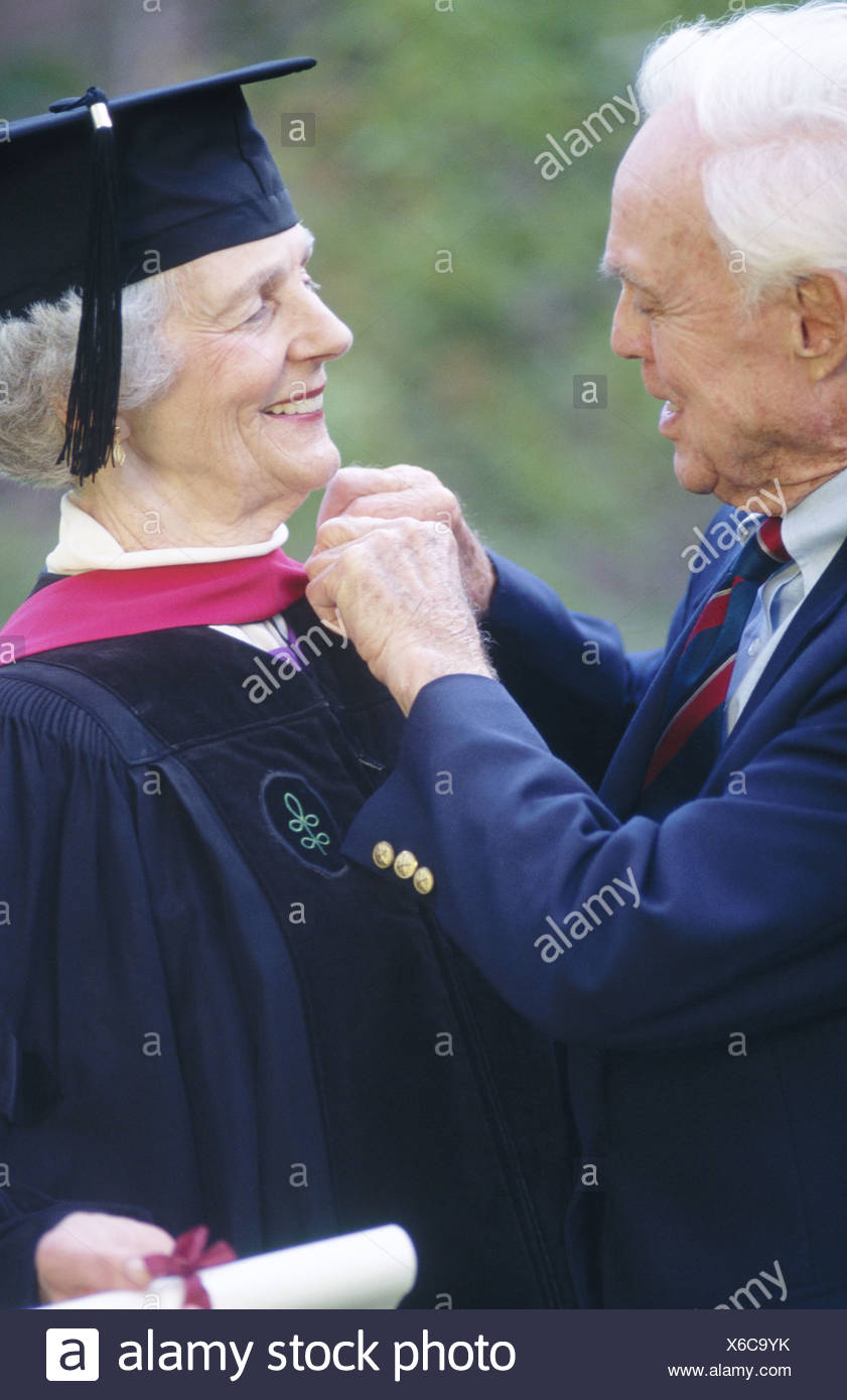 Senior woman wearing graduation cap and gown being congratulated by ...