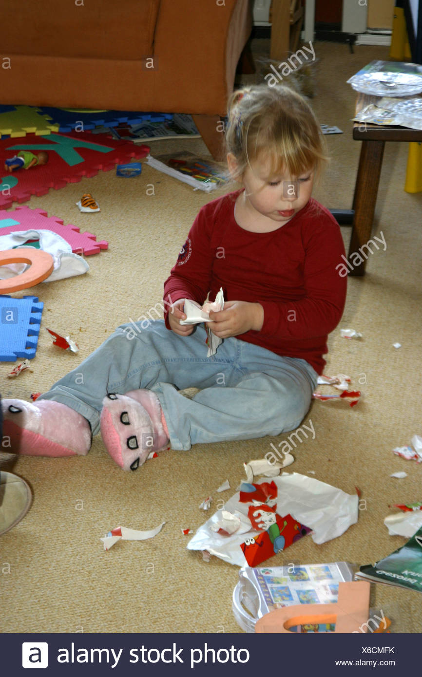 Christmas presents unwrapped and toddler girl sitting in messy ...