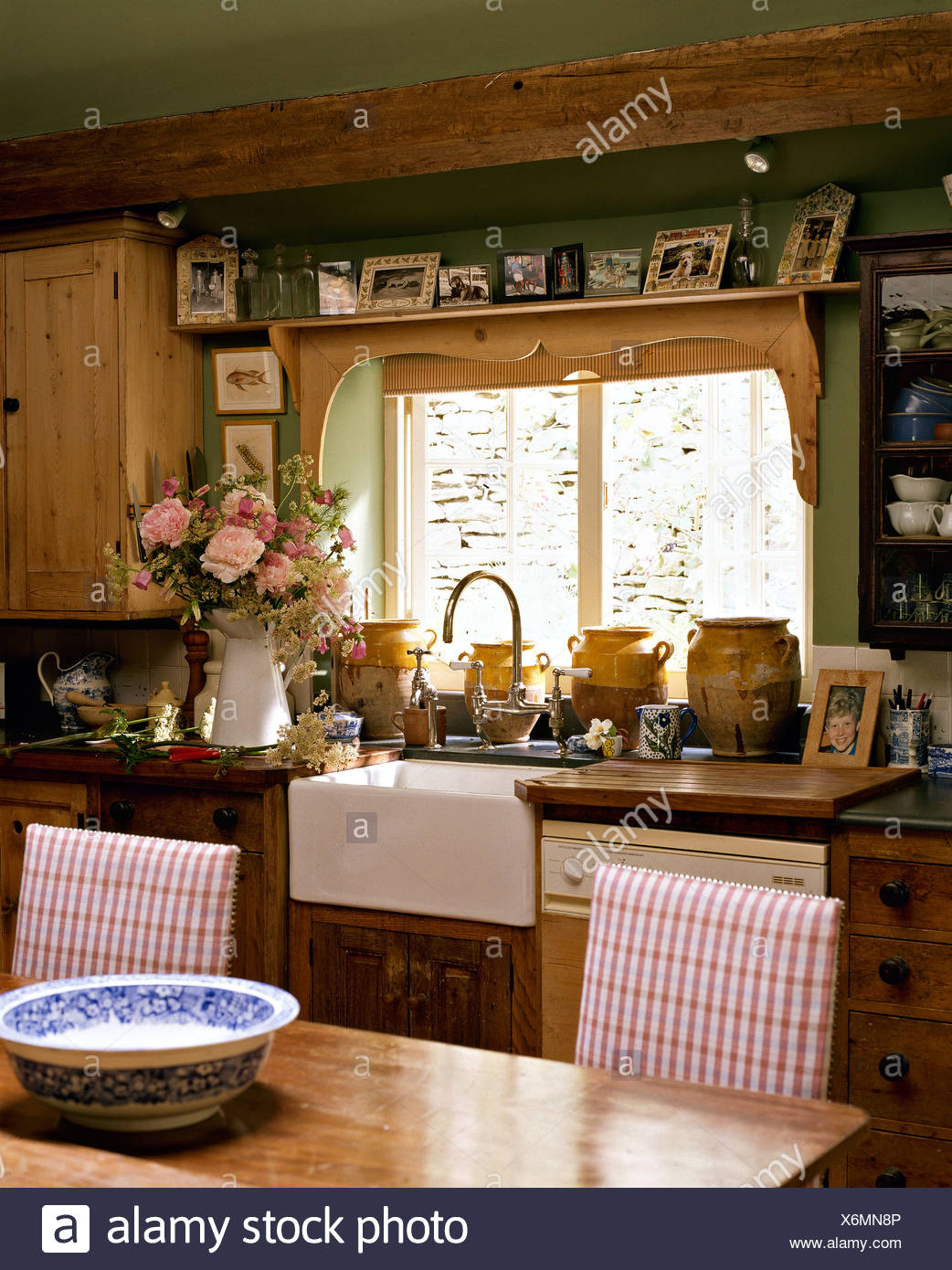 Photographs on shelf above window and Belfast sink in cottage ...