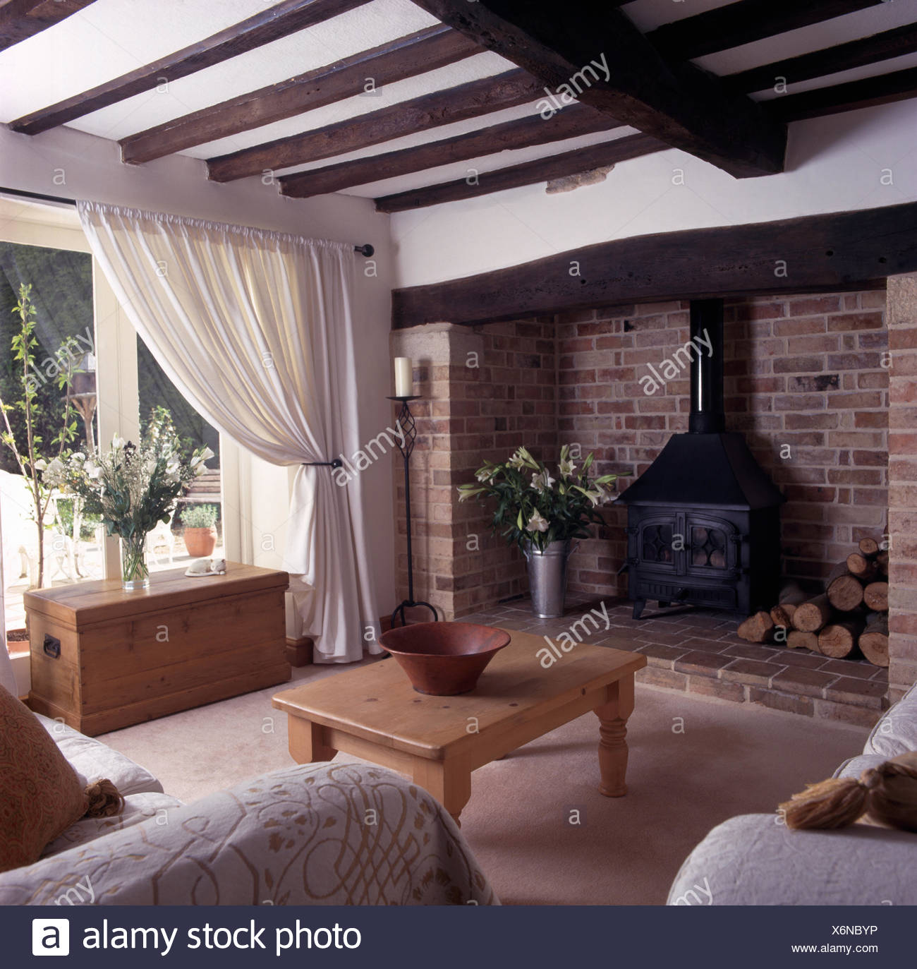 Wood Burning Stove In A Beamed Country Sitting Room With A Pine Chest In  Front Of Glass Doors With White Curtains