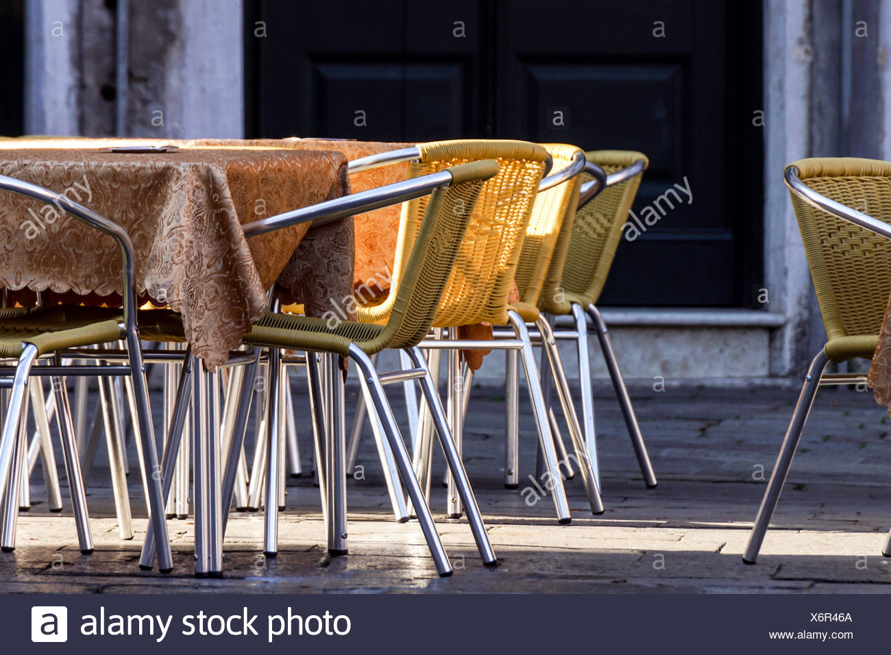 Wrought iron table and chairs outside sidewalk cafe waiting for customers to sit and dine. & Wrought iron table and chairs outside sidewalk cafe waiting for ...
