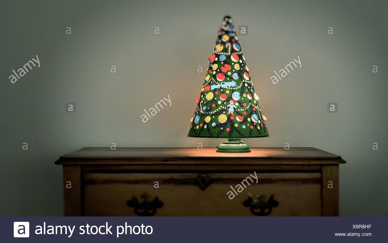 an antique christmas tree lamp spins from the heat given off by the light bulb sits on vintage chest