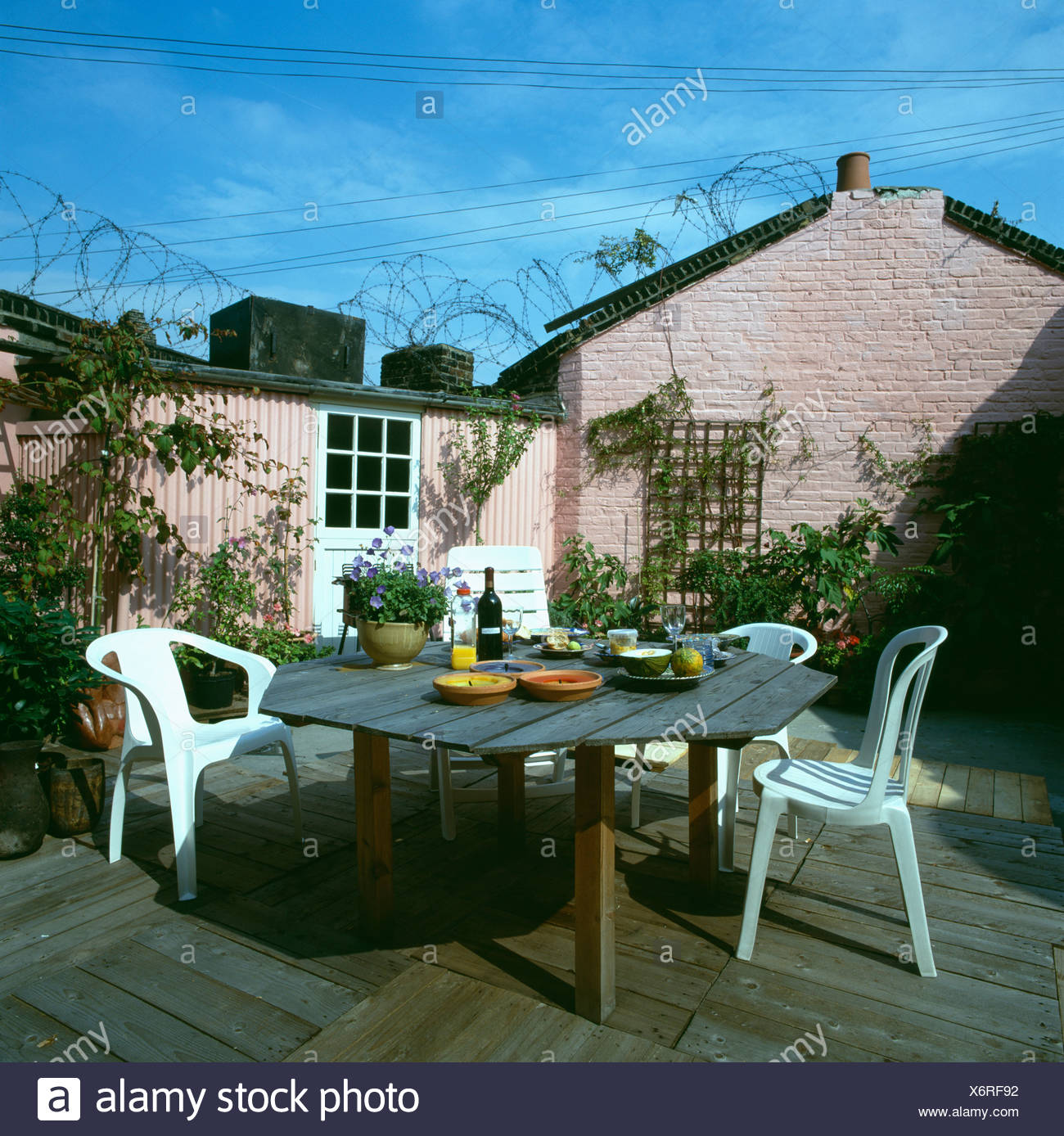 White Plastic Furniture And Wooden Table On Reclaimed Pallet Decking On  Patio Of Pink Cottage