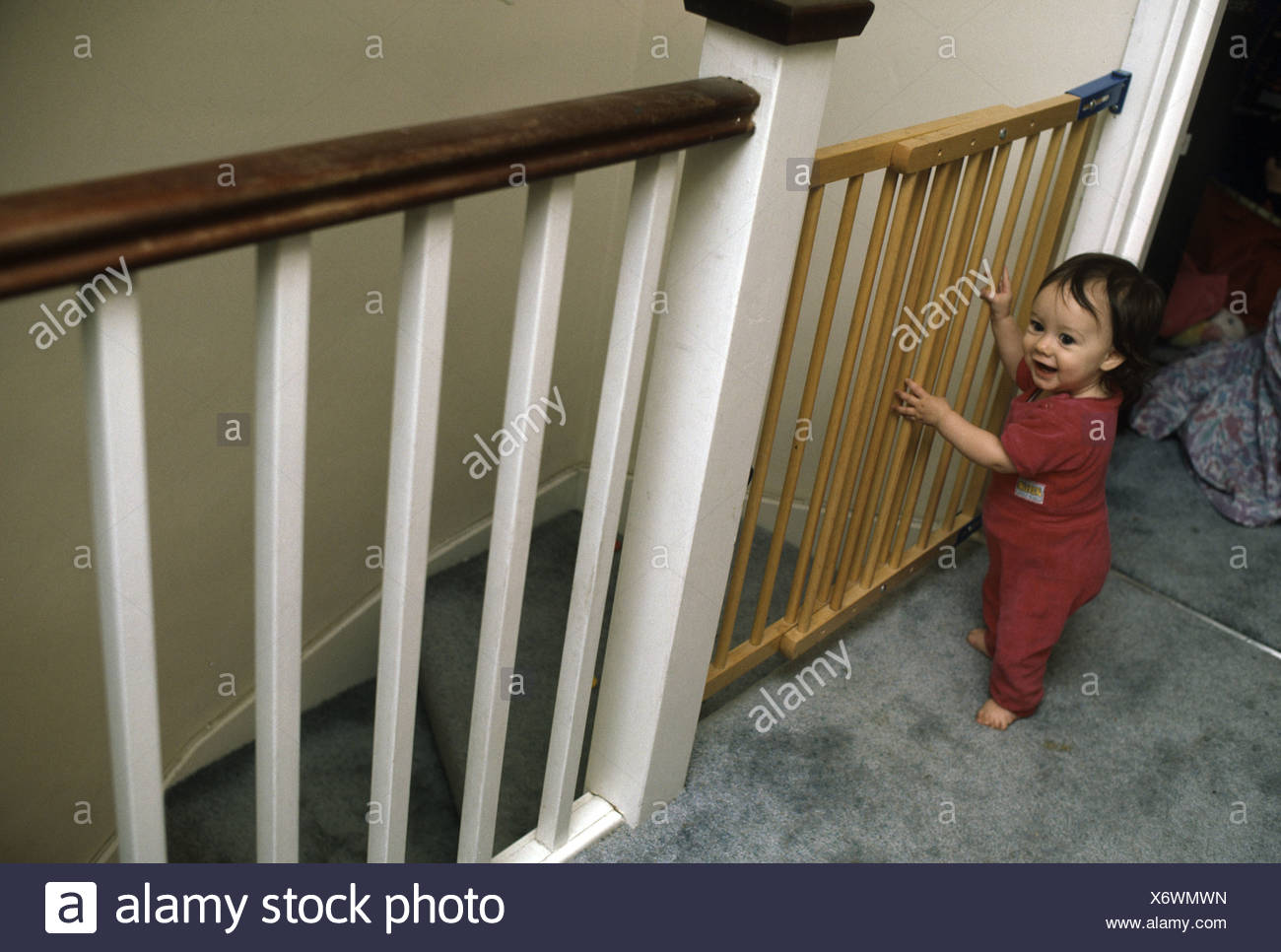 Toddler Standing In Front Of A Stair Gate Leading Down The Stairs