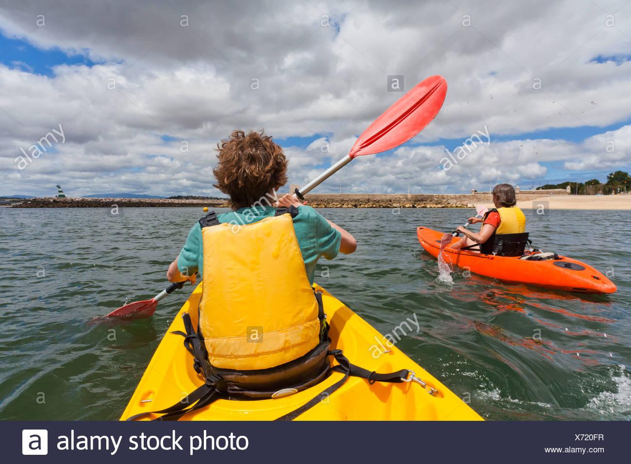 portugal lagos teenage boy mature women rowing kayak stock photo