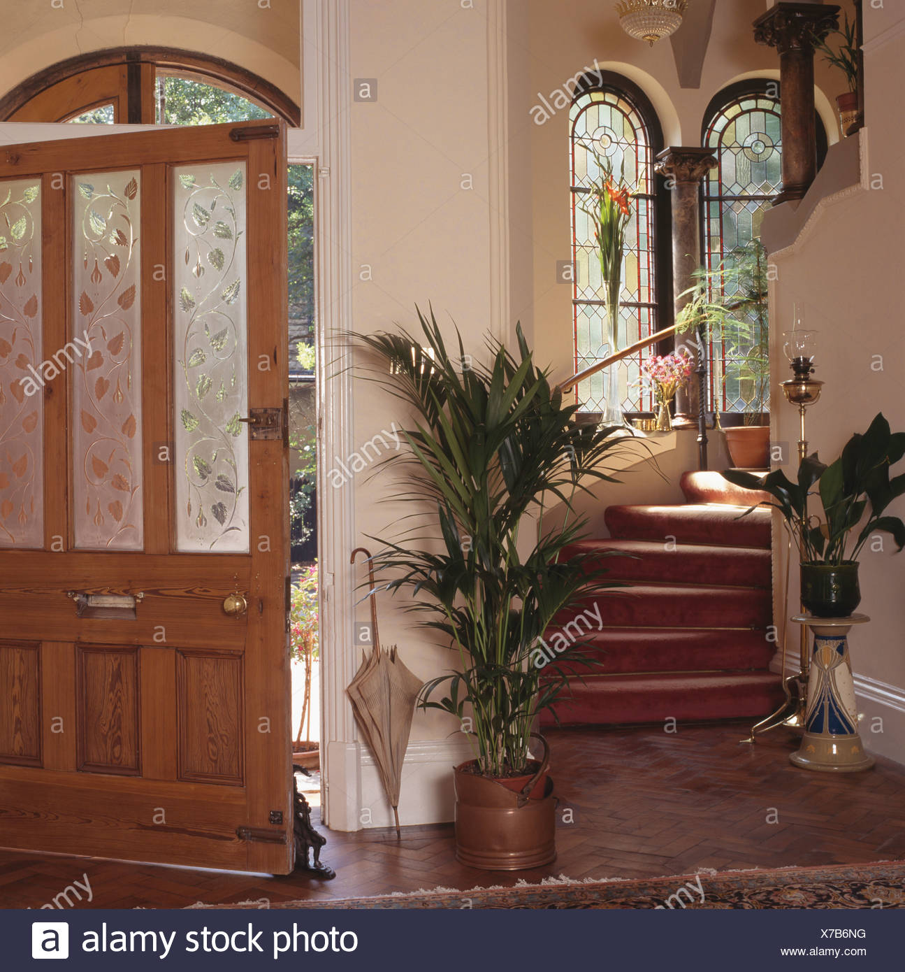 Green Houseplants On Either Side Of Staircase In Cream Hall With Open Front Door Engraved Glass Panels