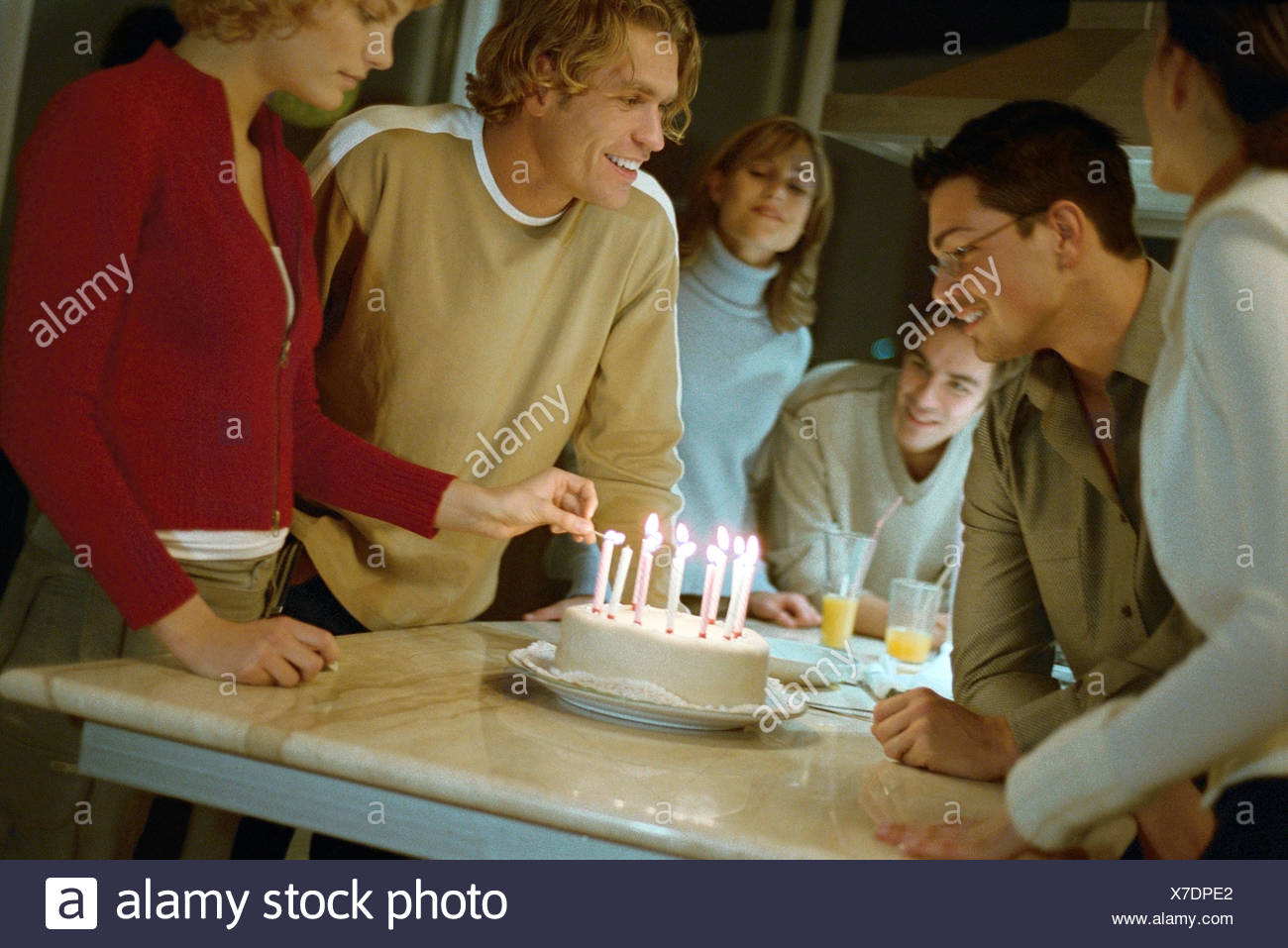 Woman Lighting Candles On Birthday Cake Friends Standing Nearby Smiling Watching