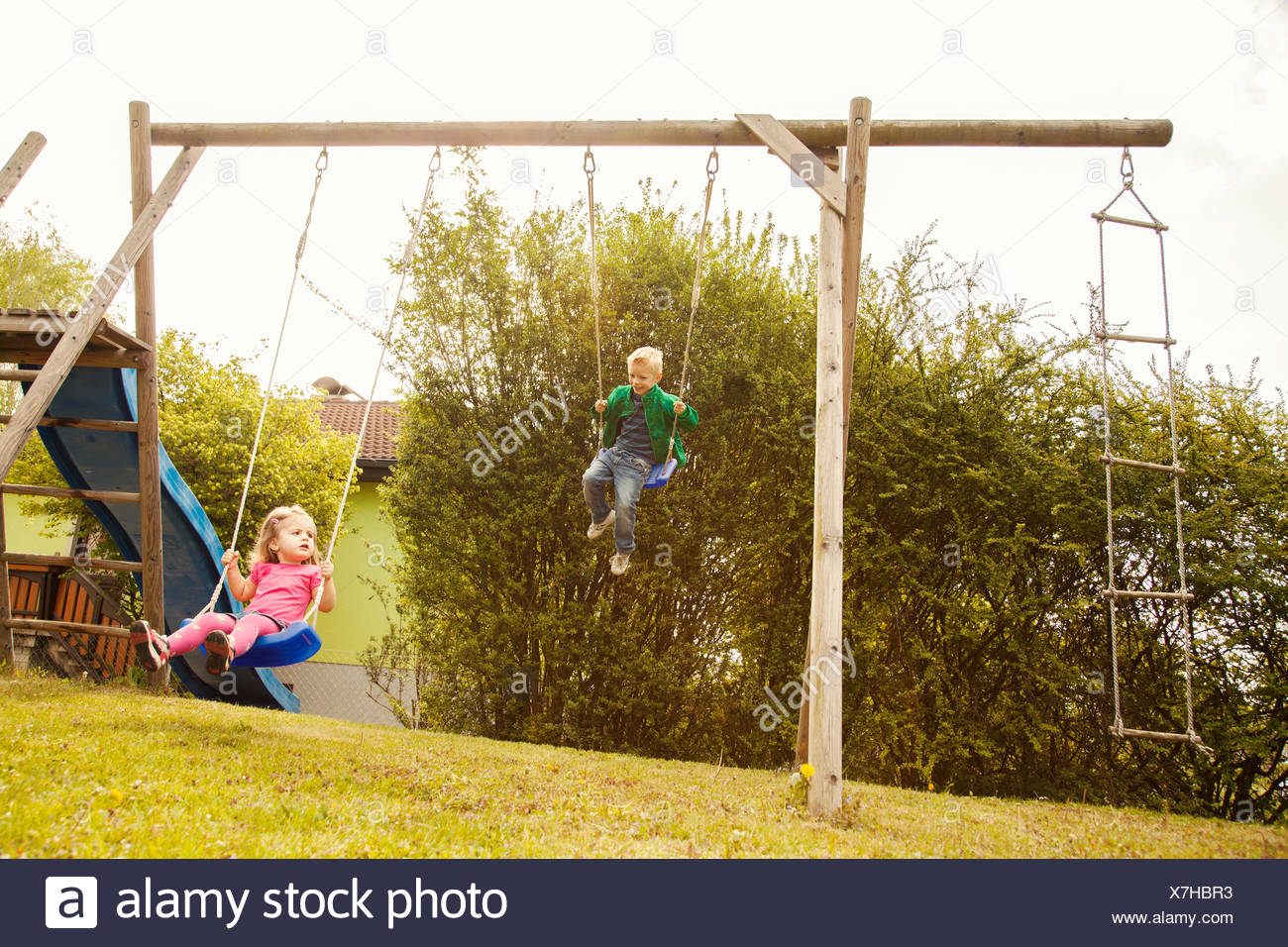 Brother and sister playing on swings in garden Stock Photo ...