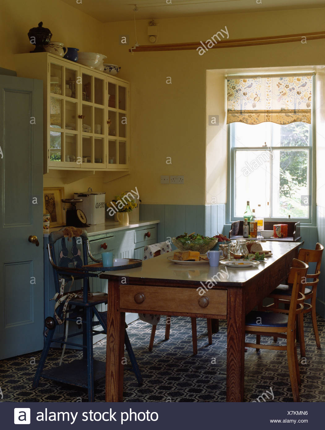 Old pine table and chairs in pale yellow kitchen with pastel blue ...