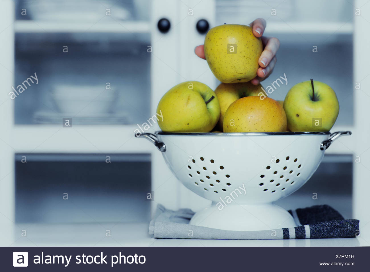 Human hand taking an apple from colander in kitchen Stock Photo ...