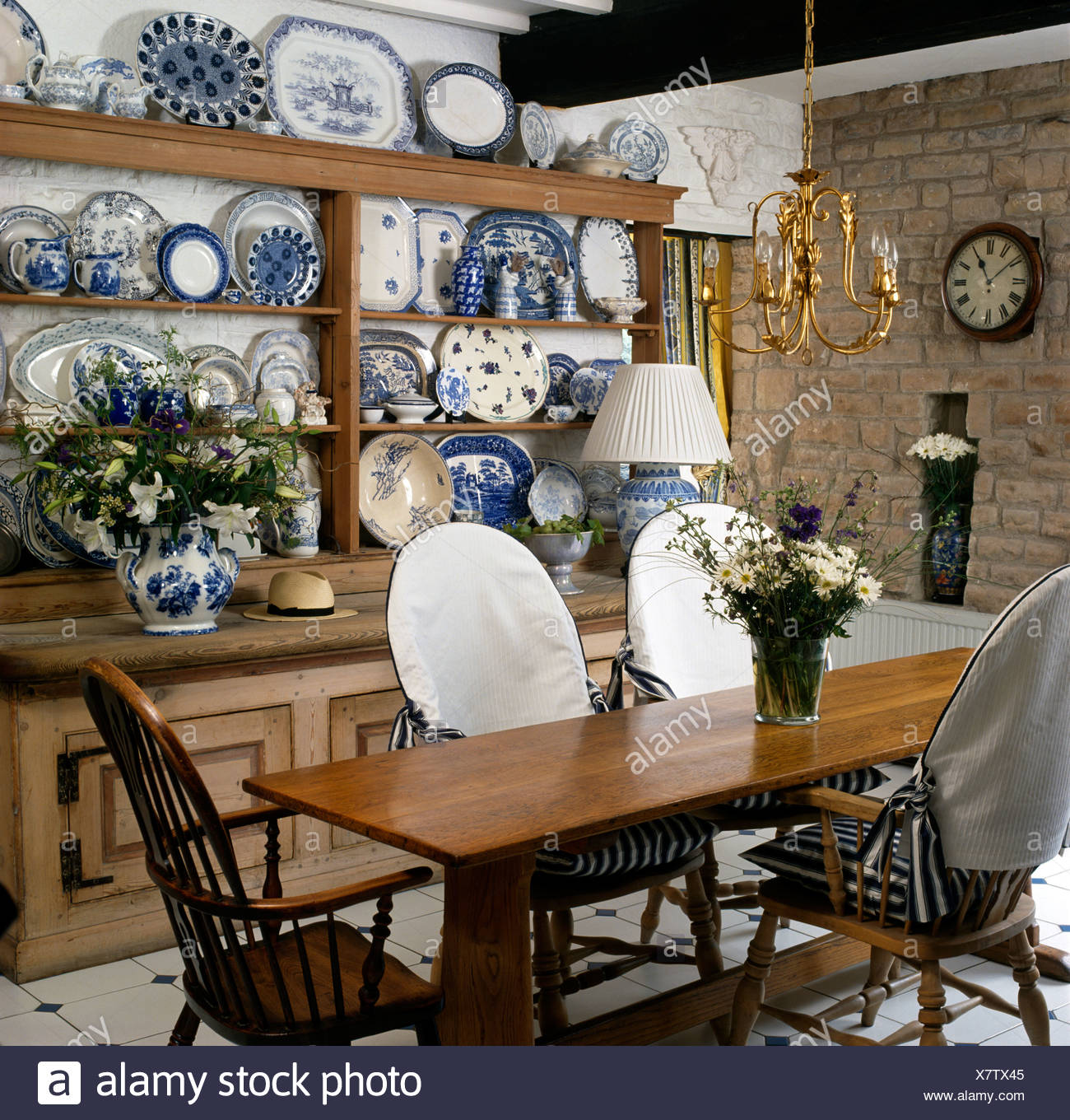 Simple Wood Table And Chairs With White Slip Covers In Cottage Dining Room  With Collection Of Blue+white China On Old Dresser