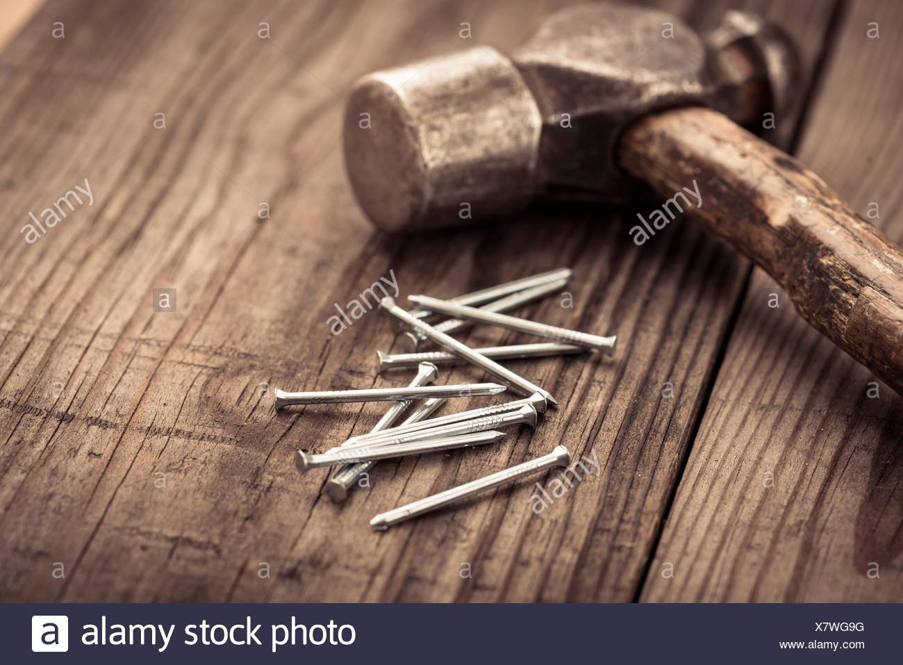 Vintage Hammer And Nails Lying On Wooden Surface Of Workbench
