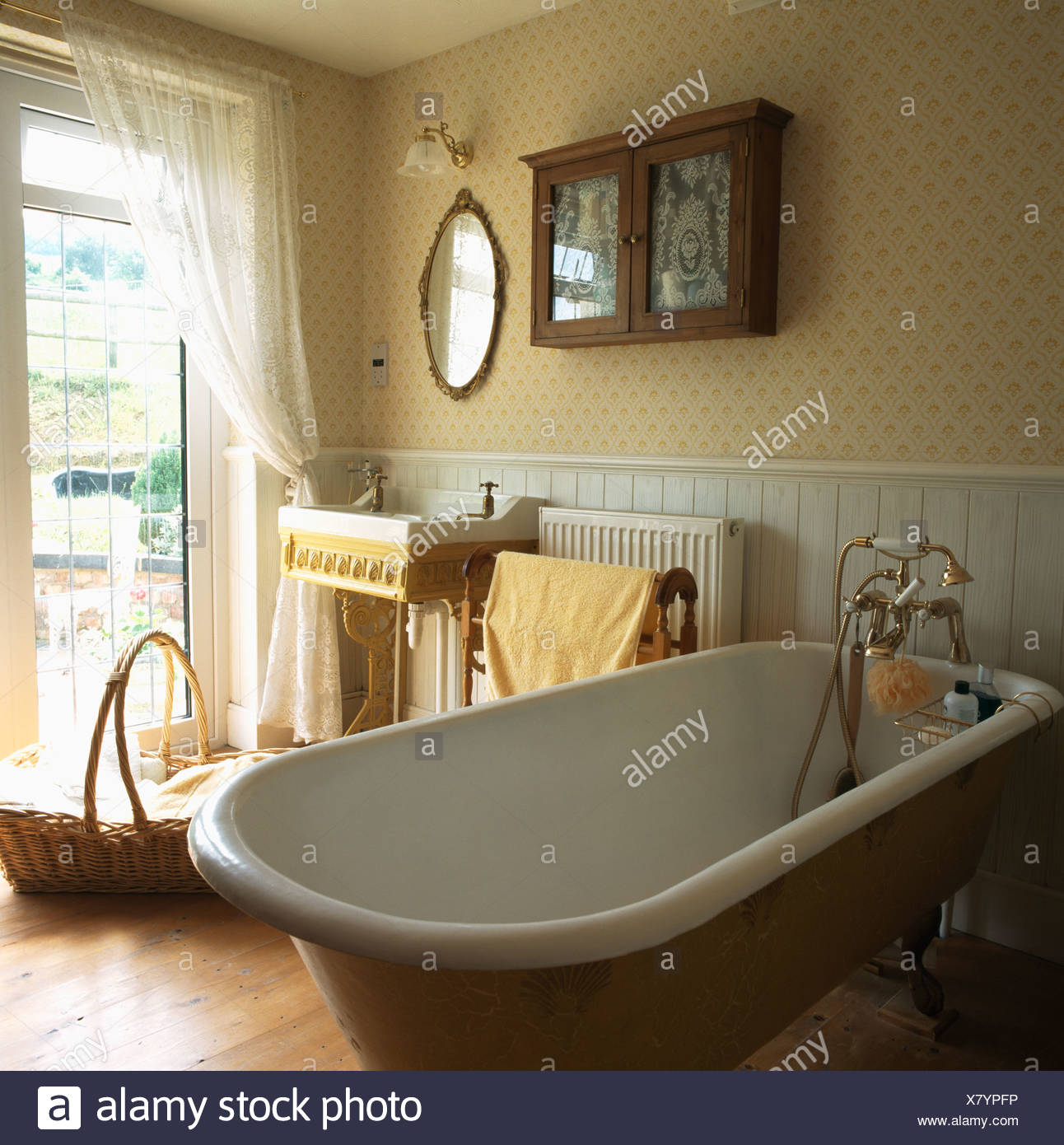 Patterned Wallpaper And Roll Top Bath In Traditional Bathroom With Old  Basin Beside French Windows With White Voile Curtains