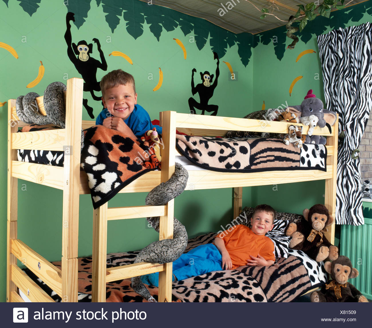 two small boys on bunk beds in nineties animal themed bedroom for