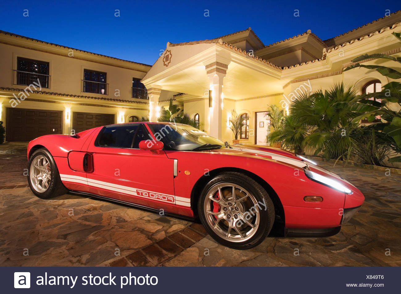 Red Ford Gt Sports Car In Front Of Spanish Villa Lit At Night