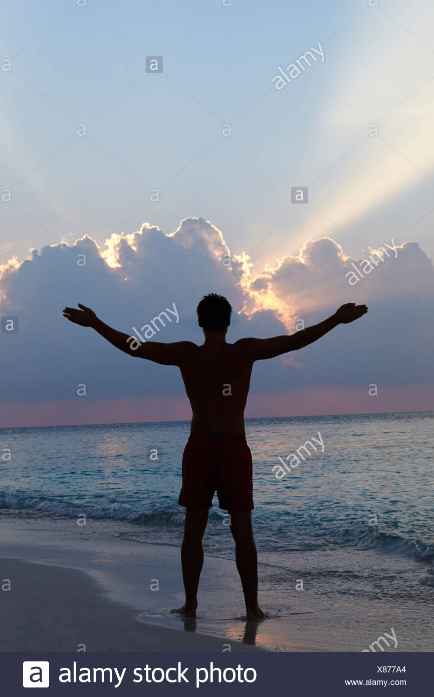 silhouette of man with outstretched arms on beach at sunset stock