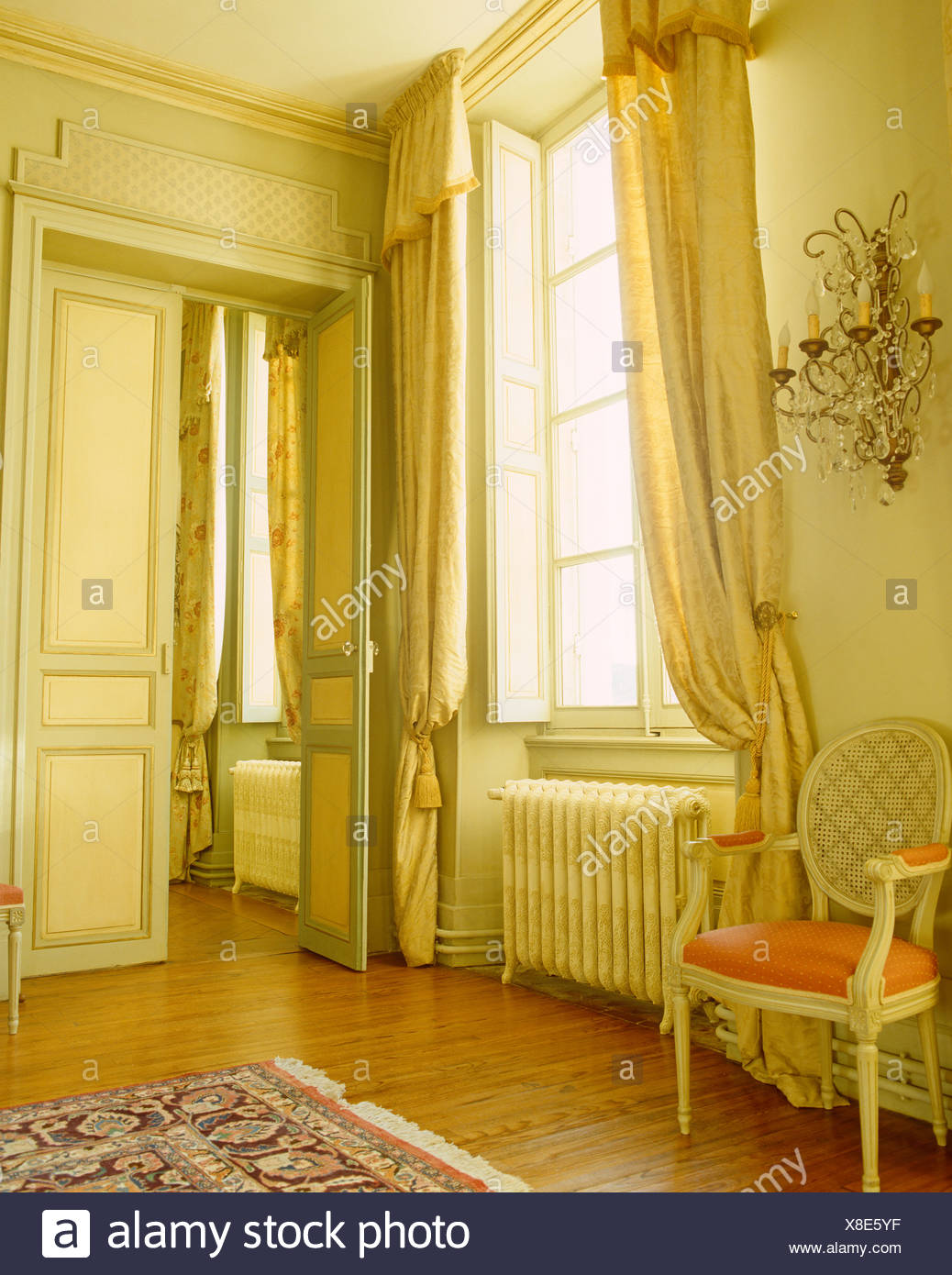 Silk drapes on tall windows in opulent French chateau dining room with painted balloon back chair and double doors & Silk drapes on tall windows in opulent French chateau dining room ...